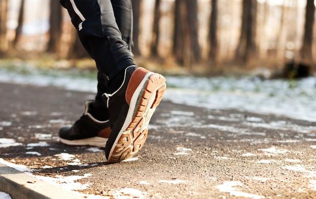 Il giovane fa jogging nel parco invernale