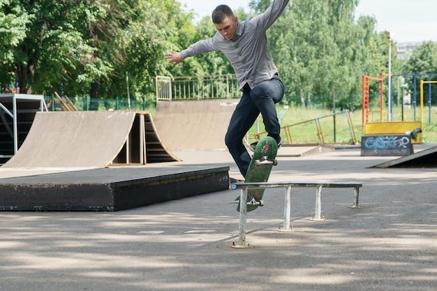 Giovane ragazzo in jeans e maglietta che fa skateboard sulle siepi nel soleggiato parco estivo