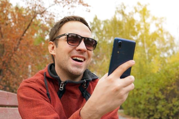 Il giovane guarda lo schermo del telefono ridendo e gioendo. comunicazione comunicazione delle persone attraverso la rete. conversazione tramite chat video. emozione gioiosa sul viso.