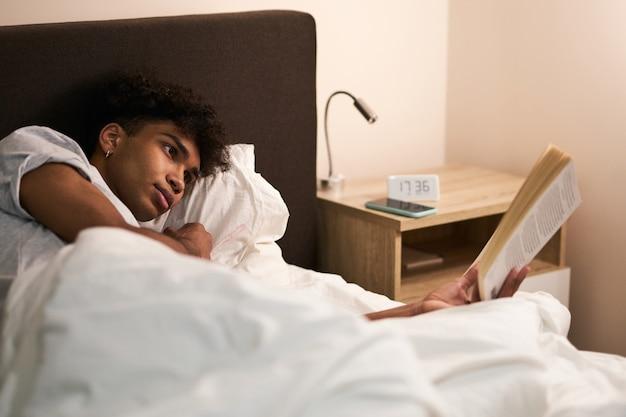 Giovane ragazzo sdraiato nel letto a casa che riposa e legge un libro interessante prima di andare a dormire