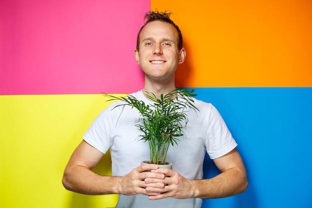 Giovane uomo con una maglietta bianca, sfondo colorato, palma decorativa, foto di emozioni, pianta domestica, amore per la natura