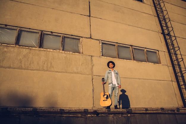 Giovane musicista con un cappello con una chitarra contro un muro di cemento.