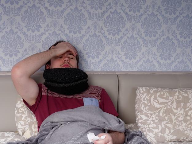 Giovane ragazzo in una maglietta rossa si siede sul letto e prende pillole per la tosse, antidolorifici e farmaci per il raffreddore, il concetto di malattia a casa