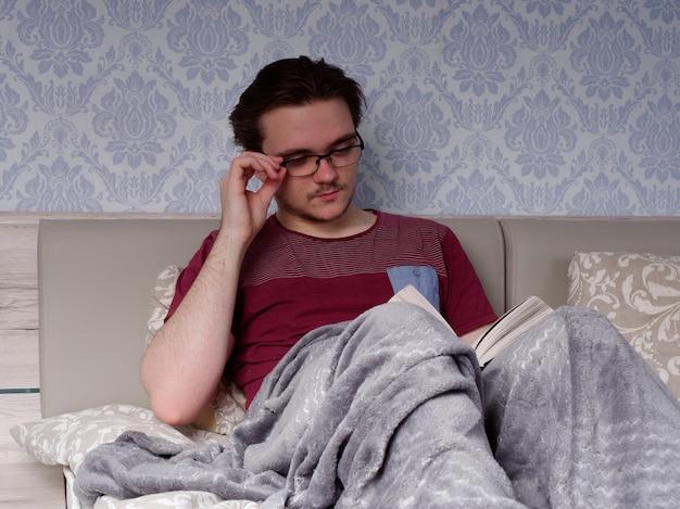 Un ragazzo con una maglietta rossa si siede su un letto di colore chiaro e legge un libro spesso, il concetto di riposo dopo una giornata di lavoro