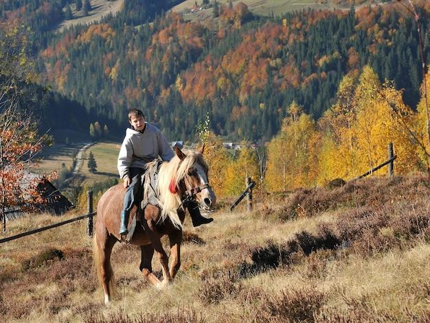 Il giovane ragazzo cavalca un cavallo in montagna