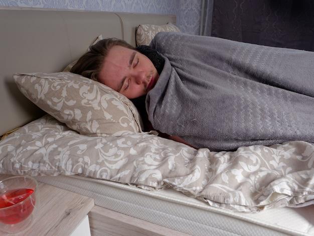 Giovane ragazzo che dorme nel letto in camera da letto dopo aver preso la medicina fredda, è malato, il concetto di malattia a casa