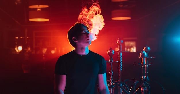 Ragazzo giovane fuma un narghilè e fa uscire una nuvola di fumo nella stanza del narghilè