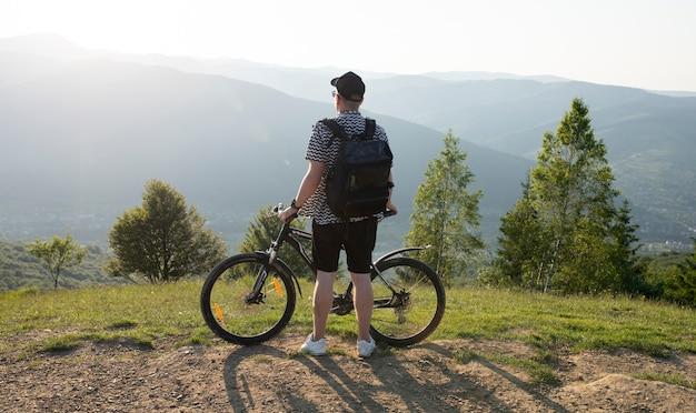 Il giovane ragazzo sta con una bicicletta sullo sfondo delle montagne