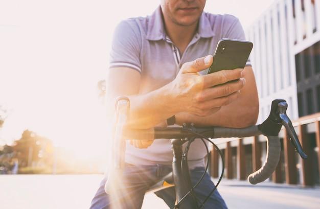 Il giovane che naviga in rete appoggiato alla sua bicicletta