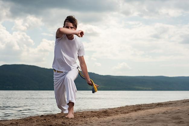 Il giovane tipo prepara il capoeira sul backround del cielo. un uomo esegue marziale il calcio nel salto