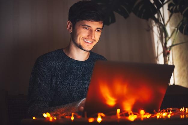 Giovane ragazzo che digita sul computer portatile in camera oscura con ghirlande sulla scrivania a casa.