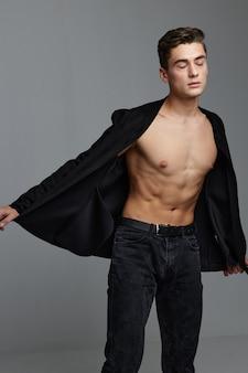 Un ragazzo con camicia e pantaloni sbottonati alza le mani ai lati. foto di alta qualità