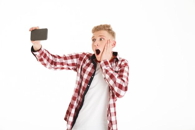 Giovane ragazzo con le parentesi graffe che prendono selfie sul telefono cellulare e che esprimono scossa o sorpresa, isolato sopra la parete bianca