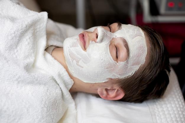 Giovane ragazzo con maschera facciale nel salone di bellezza