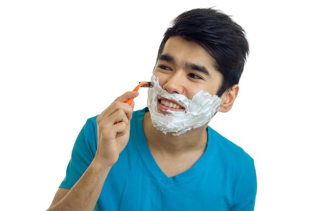 Giovane ragazzo con la schiuma sul viso distoglie lo sguardo sorridente e si rade il primo piano della barba isolato sul muro bianco