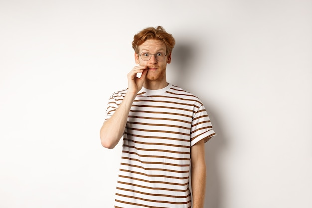 Giovane ragazzo con i capelli rossi e gli occhiali zippare la bocca, mostrando il gesto di tenuta delle labbra e sorridente, mantenendo un segreto, in piedi su sfondo bianco