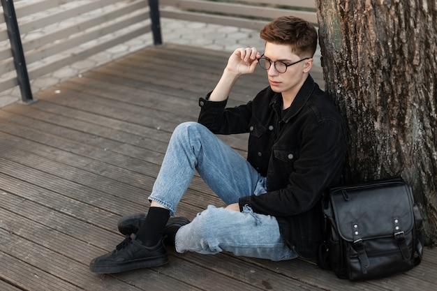 Giovane ragazzo con l'acconciatura in abiti alla moda in denim con jeans e giacca