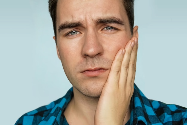 Un giovane ragazzo con un'emozione triste sul viso che tiene la mano sulla mascella del paziente su uno sfondo blu. ritratto di un uomo in espressione dolorosa con mal di denti.