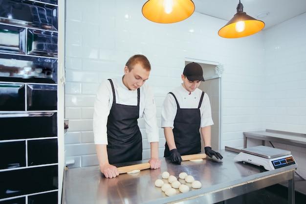 Giovani ragazzi nella panetteria che fanno i panini con la pasta
