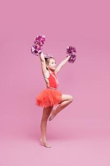 Ragazza cheerleader giovane ginnasta facendo un esercizio
