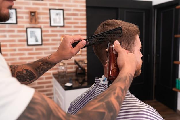 Giovane parrucchiere che taglia i capelli del cliente maschio con un tagliacapelli e un pettine in un negozio di barbiere Foto Premium