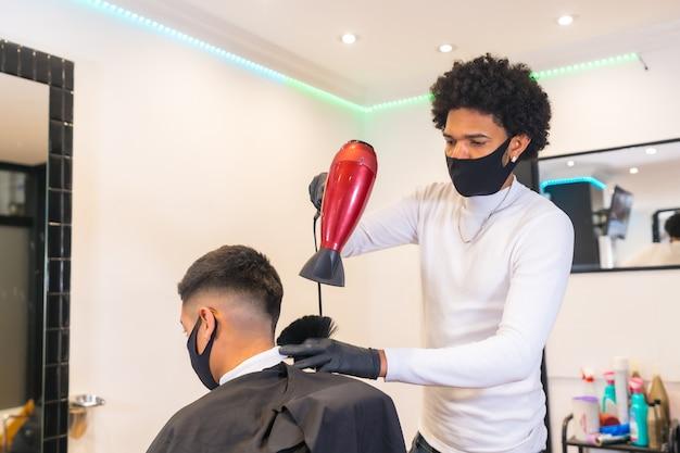 Giovane parrucchiere con maschera e guanti che asciugano i capelli del cliente con il phon. misure di sicurezza dei parrucchieri nella pandemia covid-19