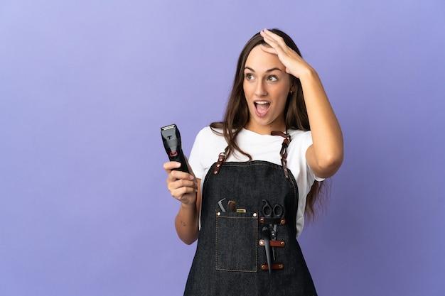 La giovane donna del parrucchiere ha isolato il fondo che fa il gesto di sorpresa mentre guarda al lato