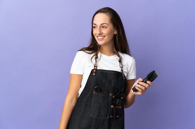 Giovane donna parrucchiere su sfondo isolato guardando al lato e sorridente
