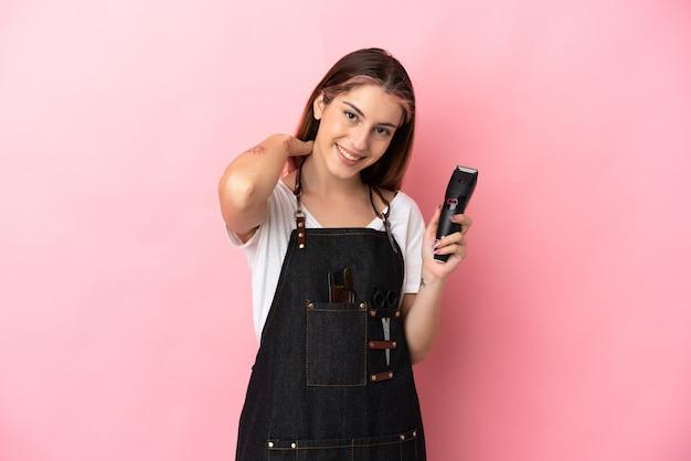 Giovane donna del parrucchiere isolata sulla risata rosa della parete