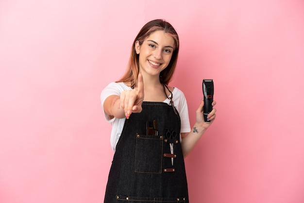 Giovane donna parrucchiere isolata sulla parete rosa che mostra e alzando un dito