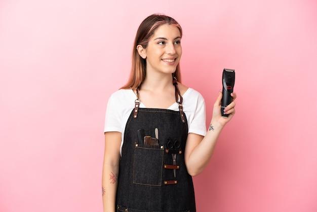 Giovane donna del parrucchiere isolata sulla parete rosa che pensa un'idea mentre osserva in su