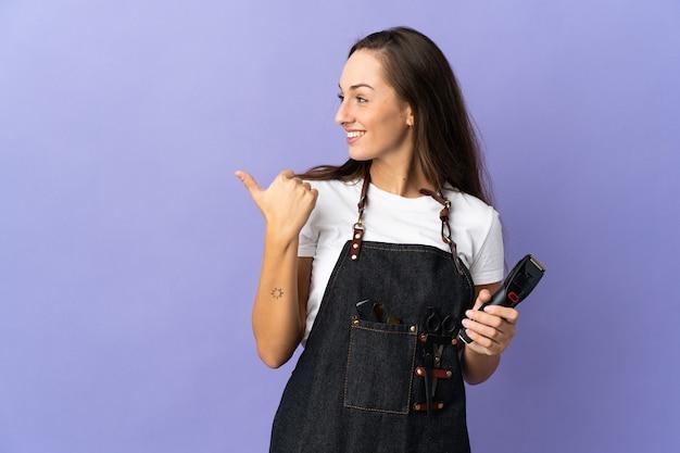 Giovane donna parrucchiere sopra la parete isolata che punta di lato per presentare un prodotto