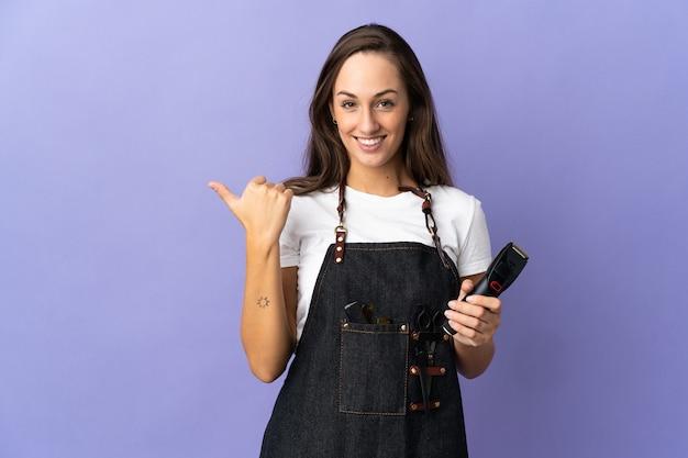 Donna giovane parrucchiere sopra la parete isolata che punta di lato per presentare un prodotto