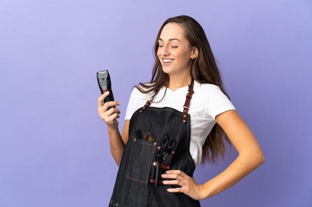 Donna giovane parrucchiere sopra la parete isolata in posa con le braccia all'anca e sorridente