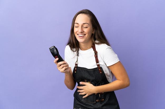 Giovane donna del parrucchiere sopra la parete isolata che sorride molto