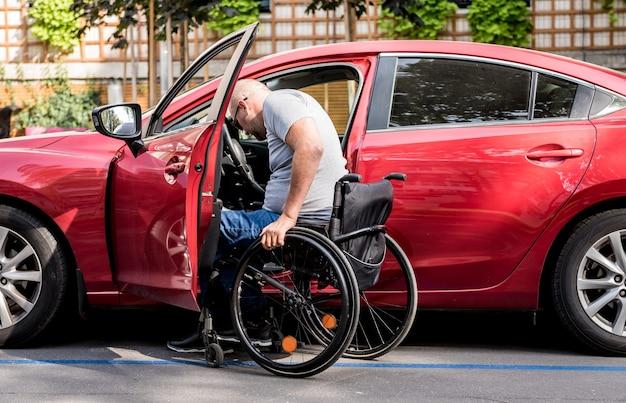 Giovane conducente handicappato che ottiene in sedia a rotelle fom macchina rossa.