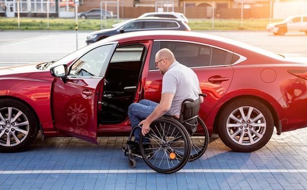 Giovane conducente disabile che sale in macchina rossa dalla sedia a rotelle