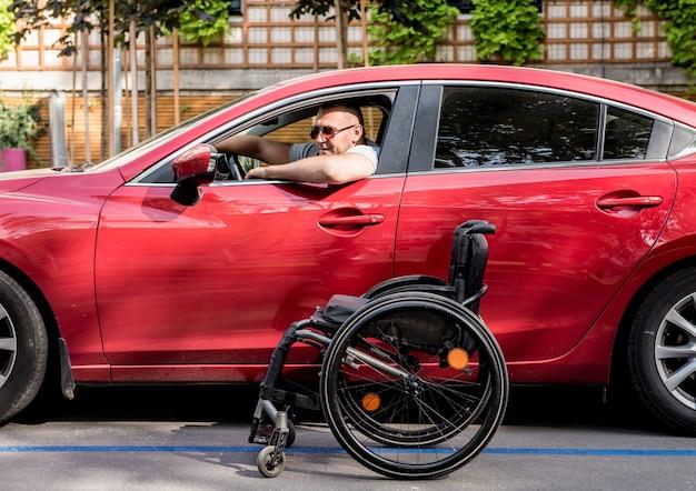 Giovane uomo disabile sul sedile del conducente della sua auto.
