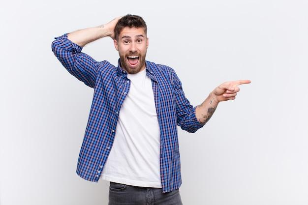 Giovane uomo di handosme che ride, che sembra felice, positivo e sorpreso, realizzando una grande idea che punta allo spazio laterale della copia contro la parete di colore