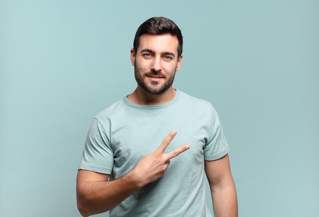 Giovane uomo adulto bello che si sente felice, positivo e di successo, con la mano che fa la forma di v sul petto, mostrando vittoria o pace