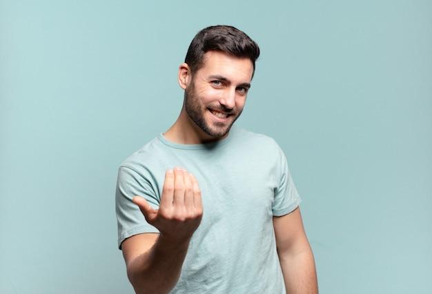 Giovane bell'uomo adulto che si sente felice, di successo e fiducioso, affronta una sfida e dice di portarlo avanti! o darti il benvenuto