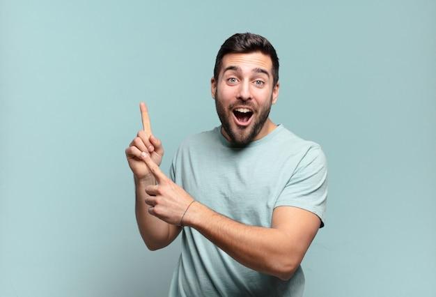 Giovane uomo adulto bello che si sente gioioso e sorpreso, sorridente con un'espressione scioccata e indicando il lato