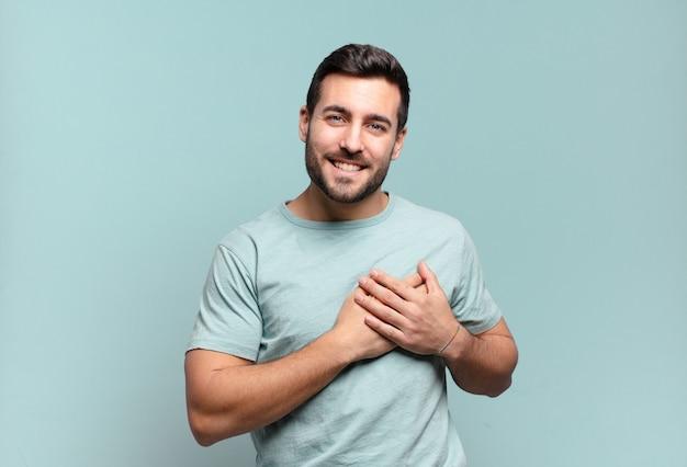Giovane uomo adulto bello sentirsi romantico, felice e innamorato, sorridendo allegramente e tenendosi per mano vicino al cuore