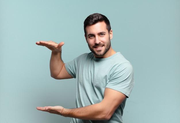 Giovane uomo adulto bello che tiene un oggetto con entrambe le mani sullo spazio della copia laterale, mostrando, offrendo o pubblicizzando un oggetto