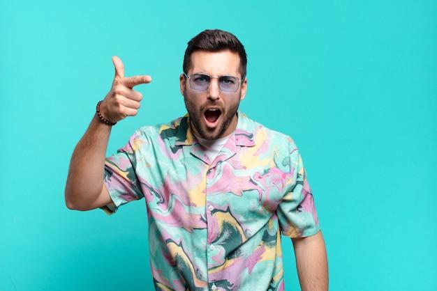 Giovane uomo adulto bello che indica con un'espressione aggressiva arrabbiata che sembra un capo furioso e pazzo. concetto di vacanze