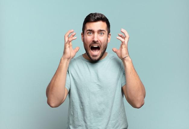 Giovane bell'uomo adulto che urla con le mani in alto, sentendosi furioso, frustrato, stressato e turbato