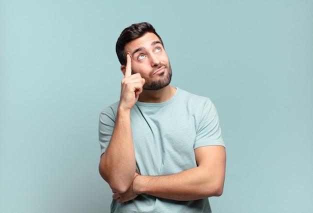 Giovane uomo adulto bello con uno sguardo concentrato, chiedendosi con un'espressione dubbiosa, guardando in alto e di lato