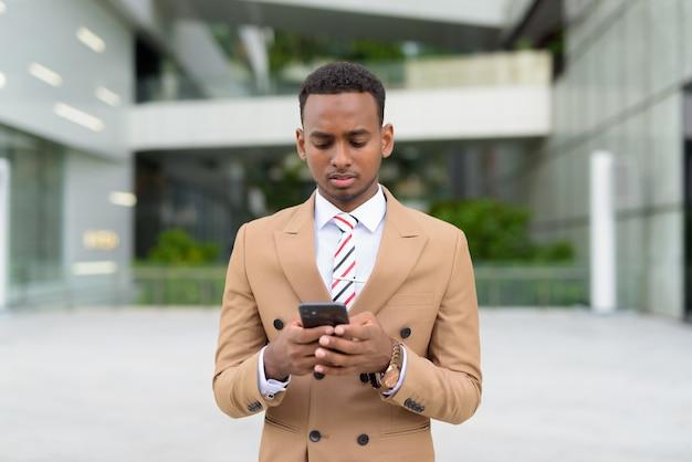 Bel giovane uomo d'affari africano utilizzando il telefono in città all'aperto