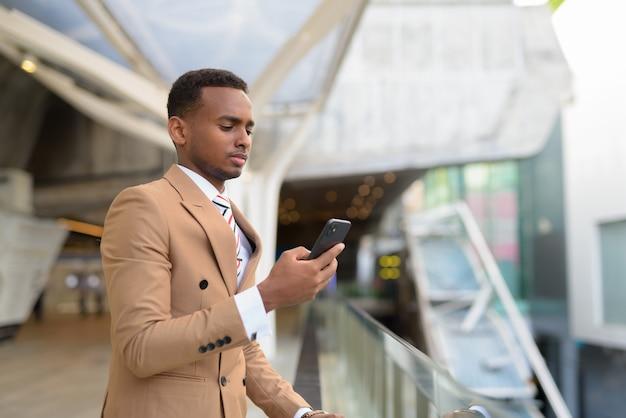 Bel giovane uomo d'affari africano utilizzando il telefono in passerella in città