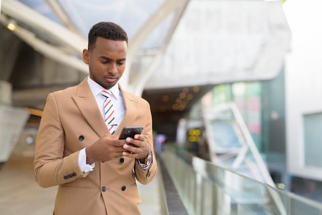 Bel giovane uomo d'affari africano utilizzando il telefono presso la passerella